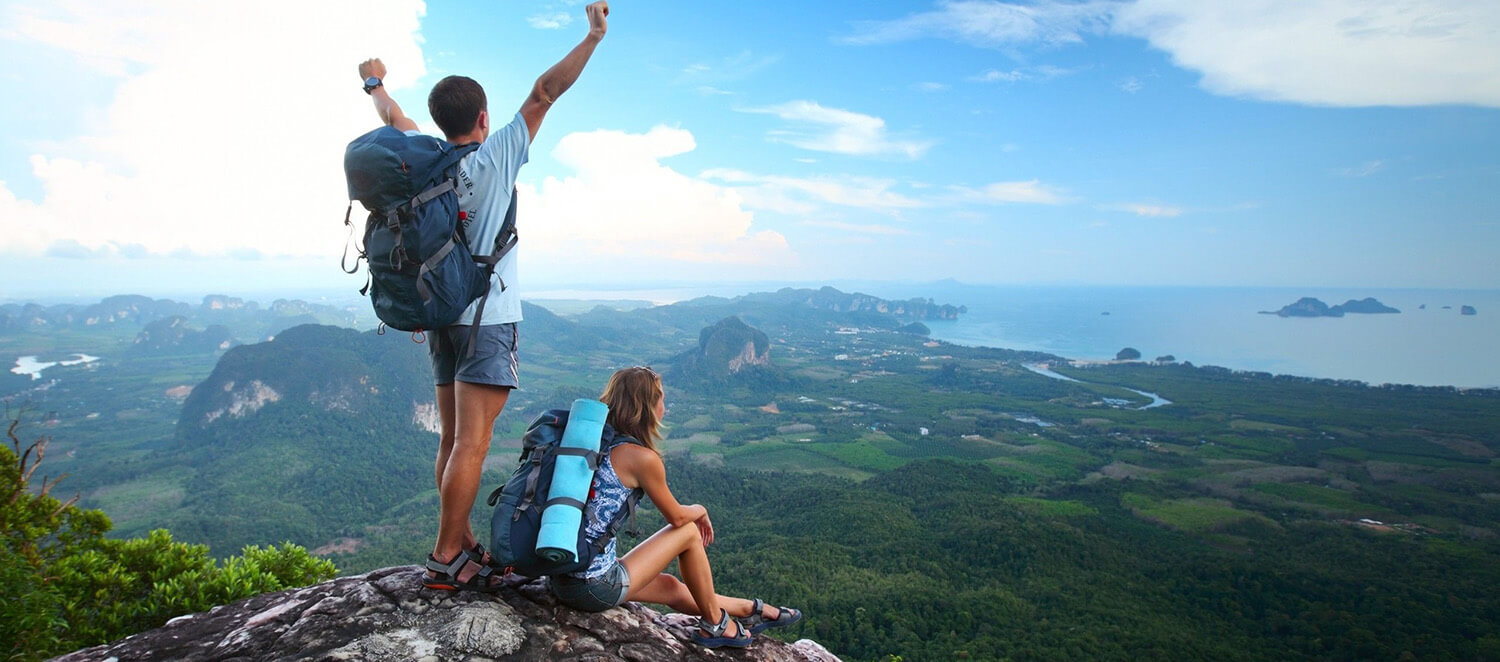 PEOPLE WITH CAMP BACKPACKS ON A MOUNTAIN HIGH WITH SEA BACKGROUND